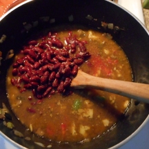 Add the beans, tomatoes, and vegetable stock, stir to combine...