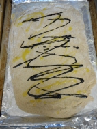 Drizzle oil and balsamic sauce on the dough, spread evenly with back of a spoon.